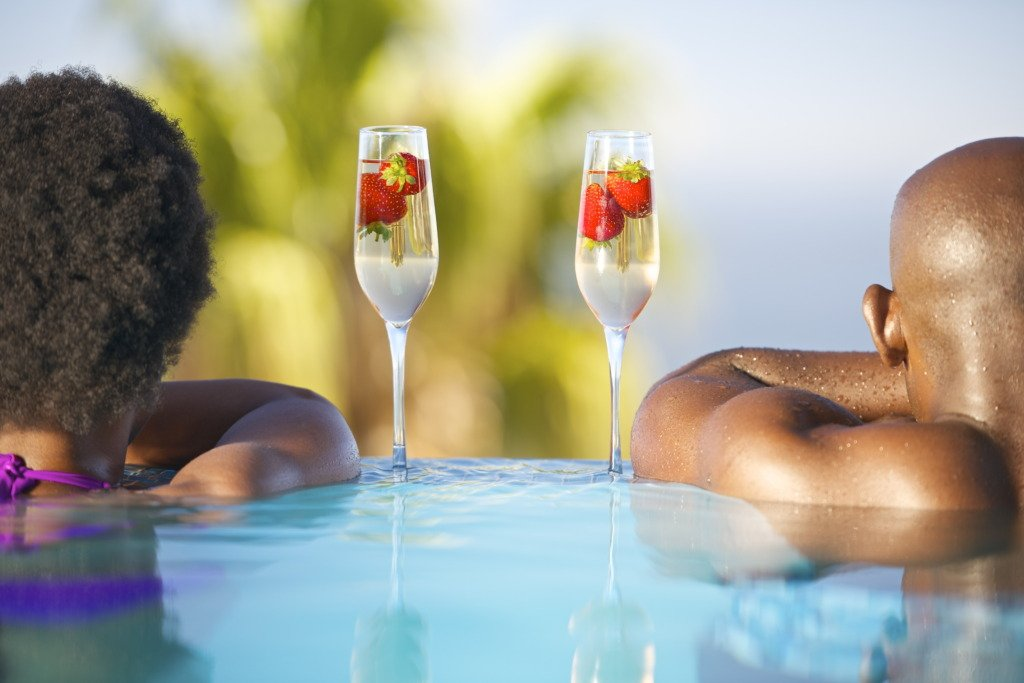 African man and woman in swimming pool with glasses of champagne.