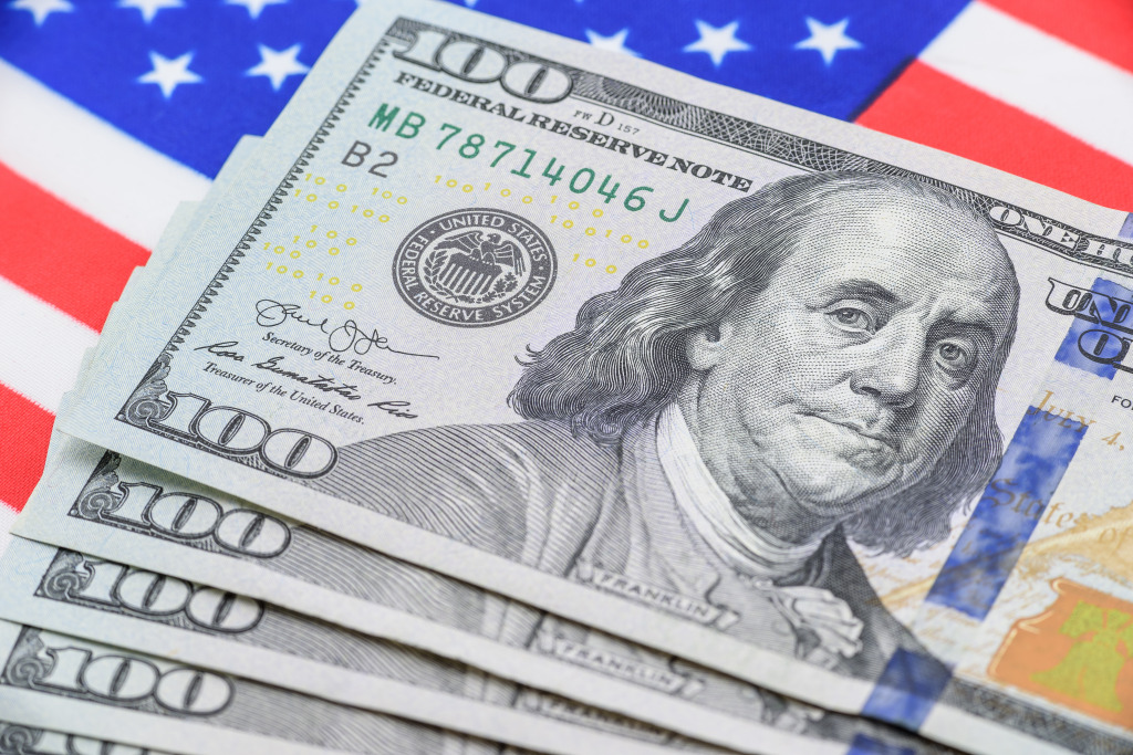 $100 bills on a background of the US flag, reflecting the concept of the dollar as a safe haven asset.