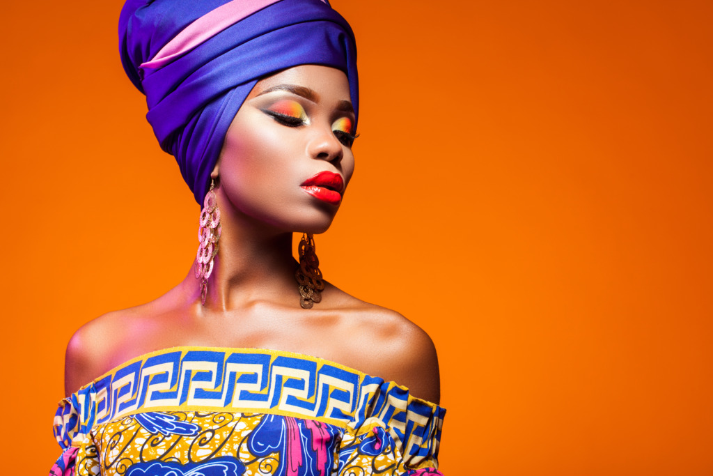 African woman in a bright dress on orange background.
