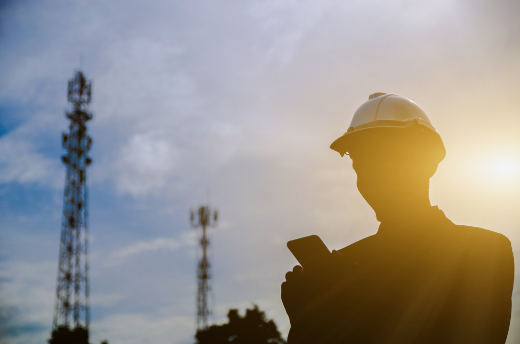 Silhouette of engineer holding a mobile phone with telecommunication antenna and sunset background.