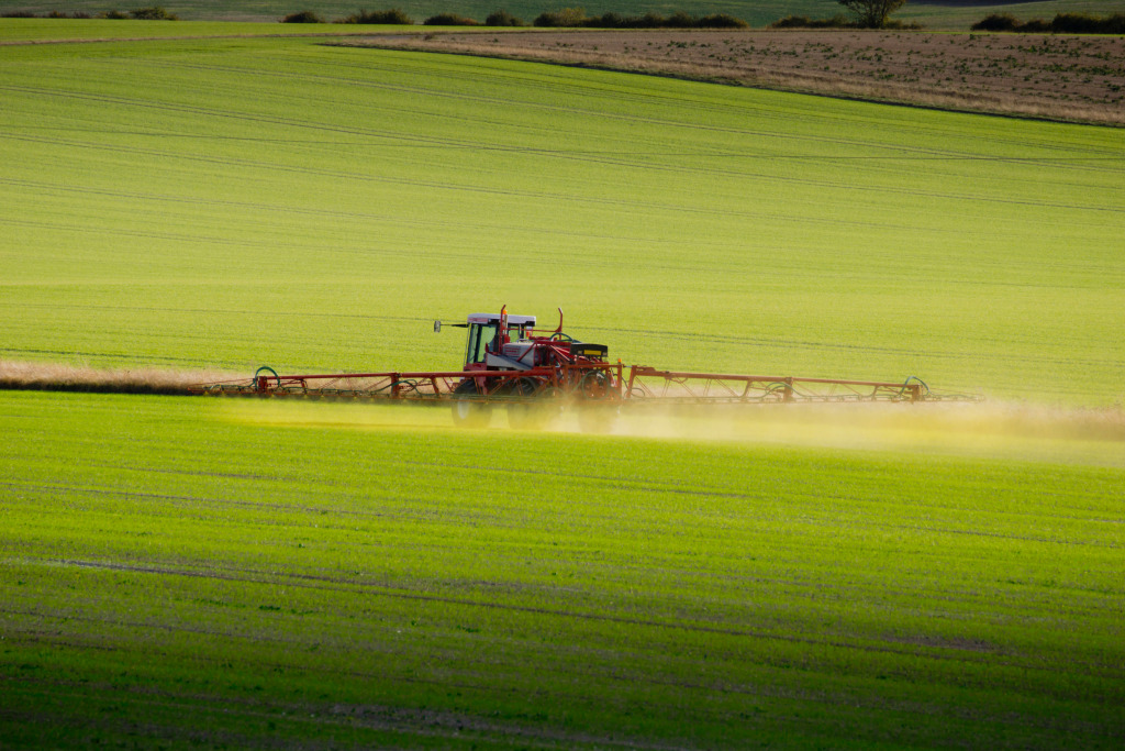 An agricultural tractor with outspread spraying arms spreads green chemicals on a field.