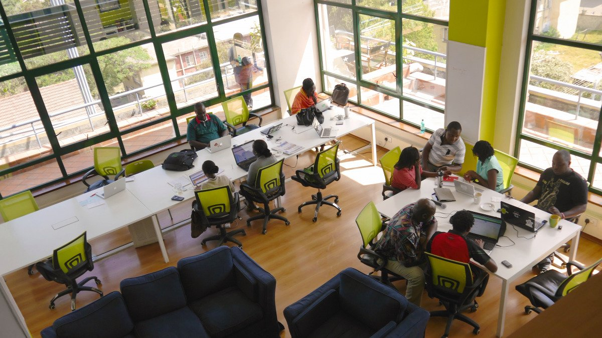 Aerial view of shared office space in Nairobi, with people sitting at desks with laptops.