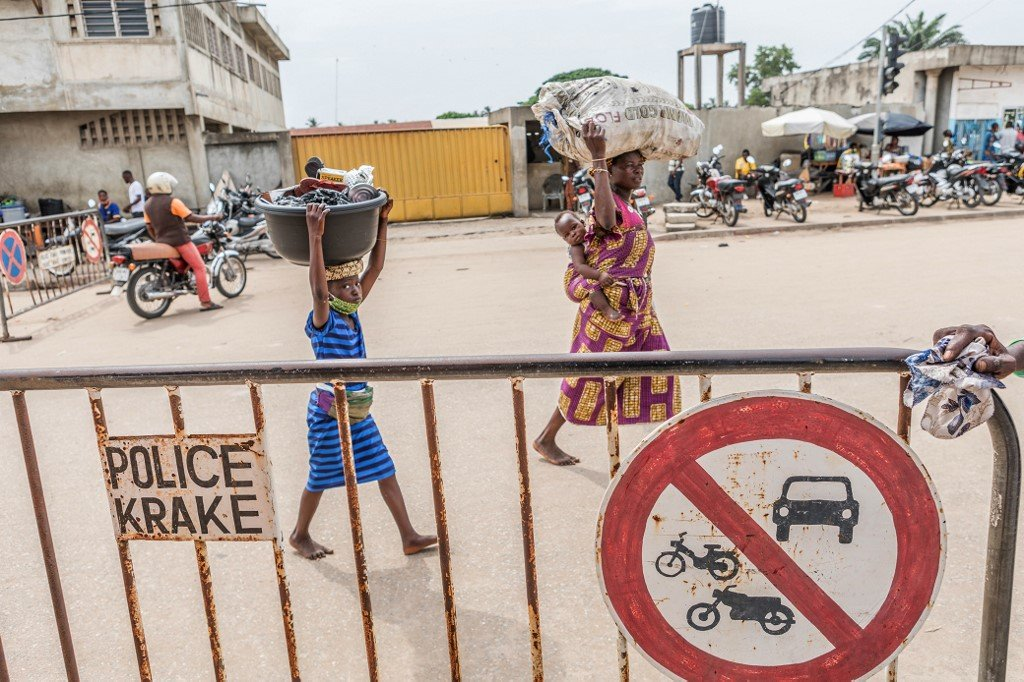 People carry merchandise across the Benin-Nigeria border one day after Nigeria announced the lifting of border closures.