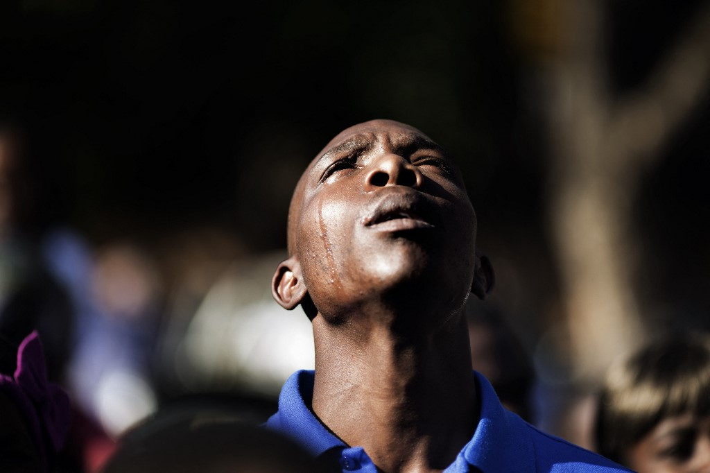 A member of the Babina na Morena gospel choir cries as he performs with his group.