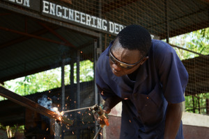 Young welder grinding metal in vocational training centre in Kakuma refugee camp.