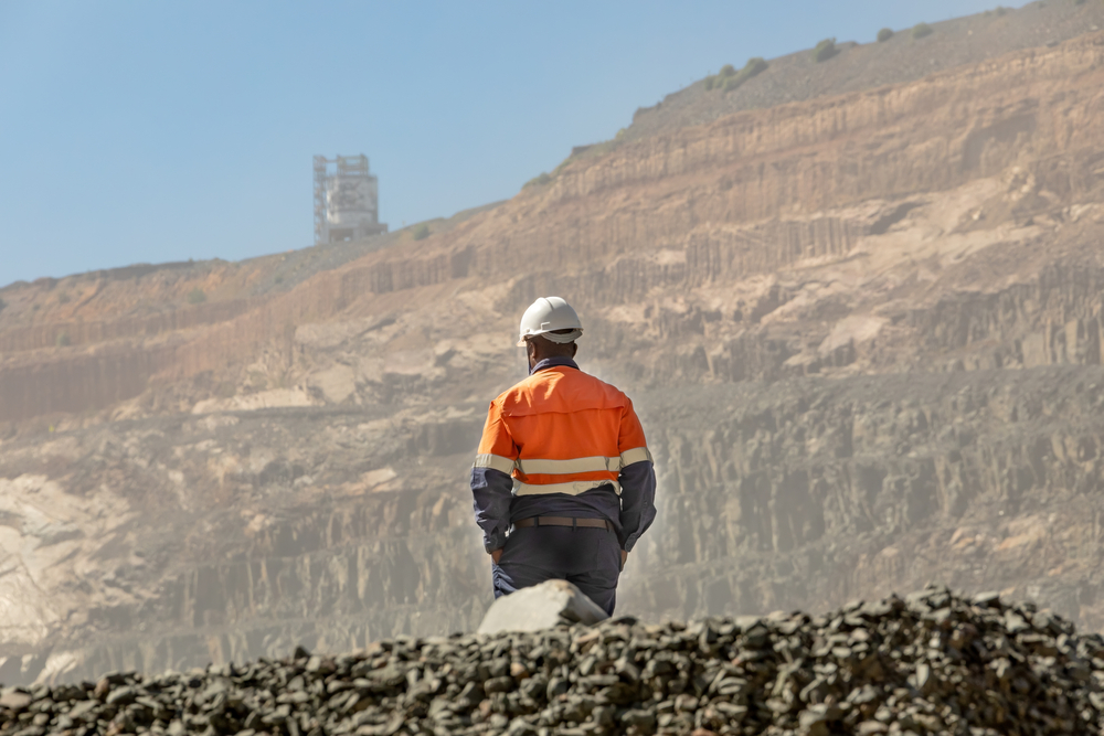 African worker looks across an open pit diamond mine.