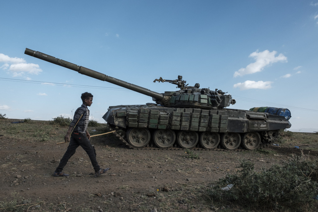 A shepherd walks past an abandoned tank belonging to Tigrayan forces. south of the town of Mehoni, Ethiopia.