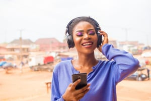 Young African woman listens to music on headphones.