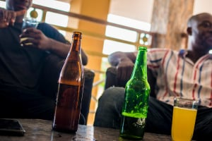 Young African men drinking beer in a bar.