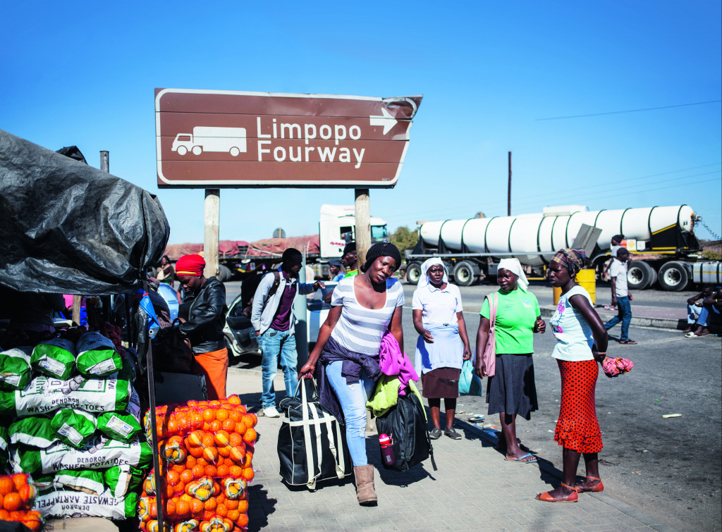 A woman carrying bags walks towards the Beitbridge border crossing between South Africa and Zimbabwe.