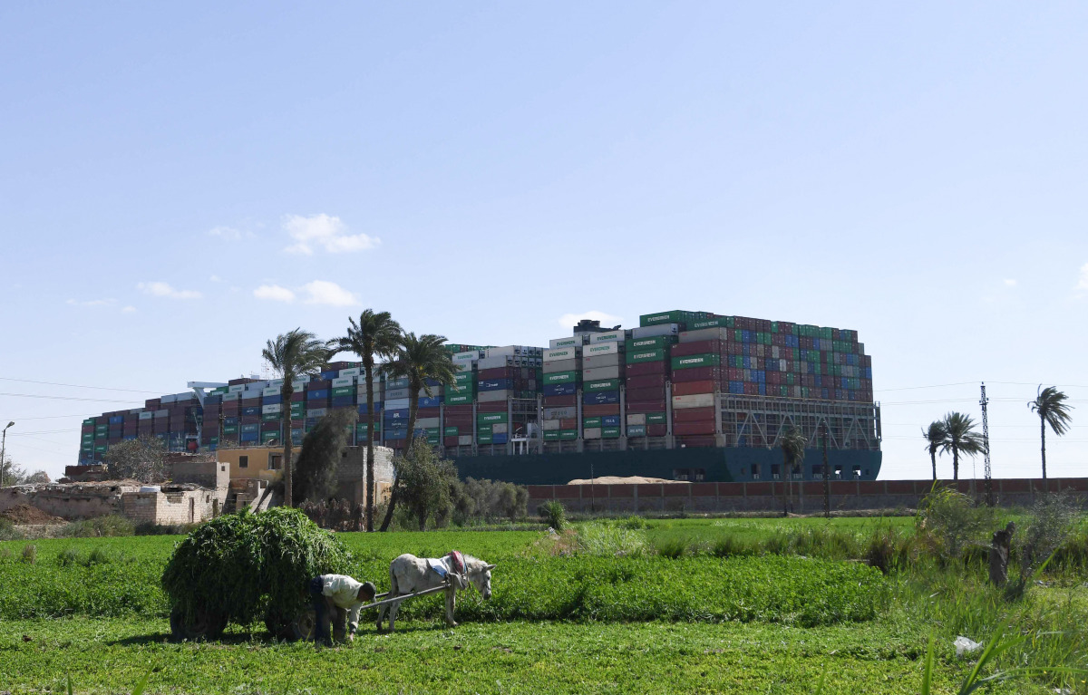 A farmer tends his field near the Suez Canal, where the stranded Ever Given container ship towers above him.