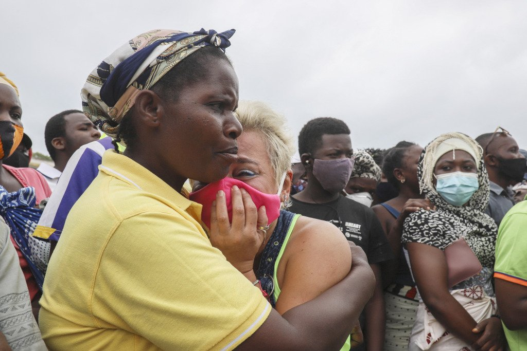 A crying woman is comforted as she waits for her son to arrive in a boat of evacuees from Palma in Mozambique.