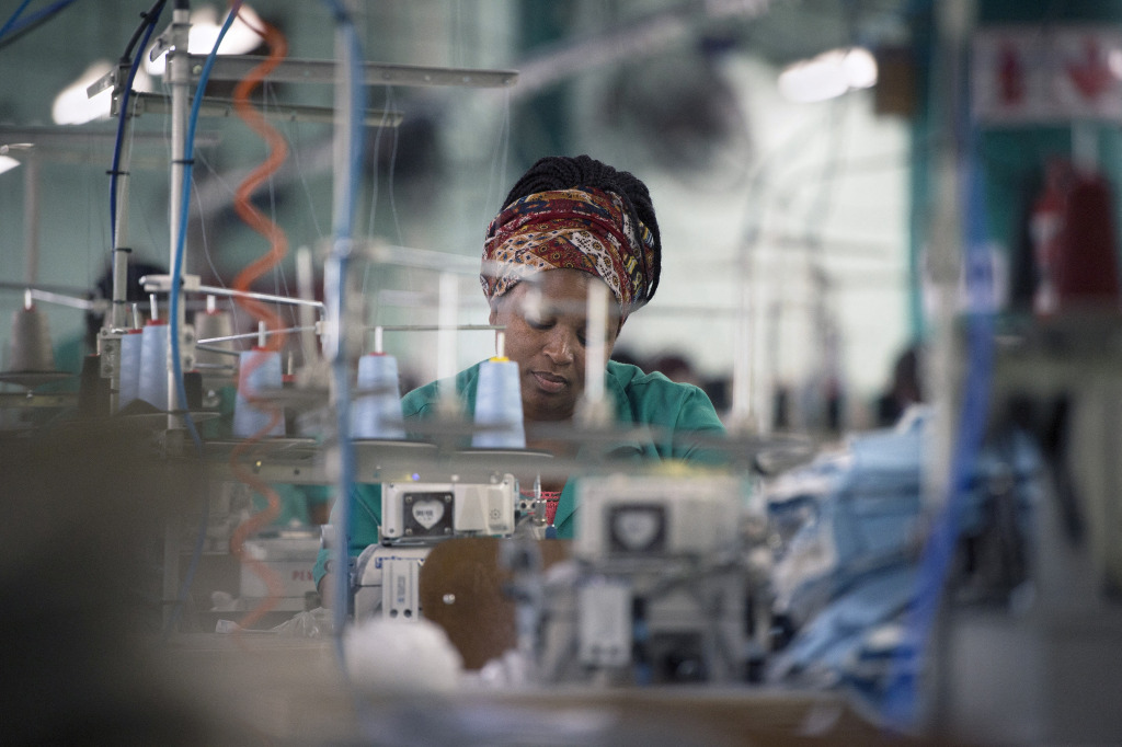 A female South African textile worker operates a loom.