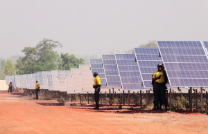 People stand by solar panels at the Zagtouli solar energy plant.
