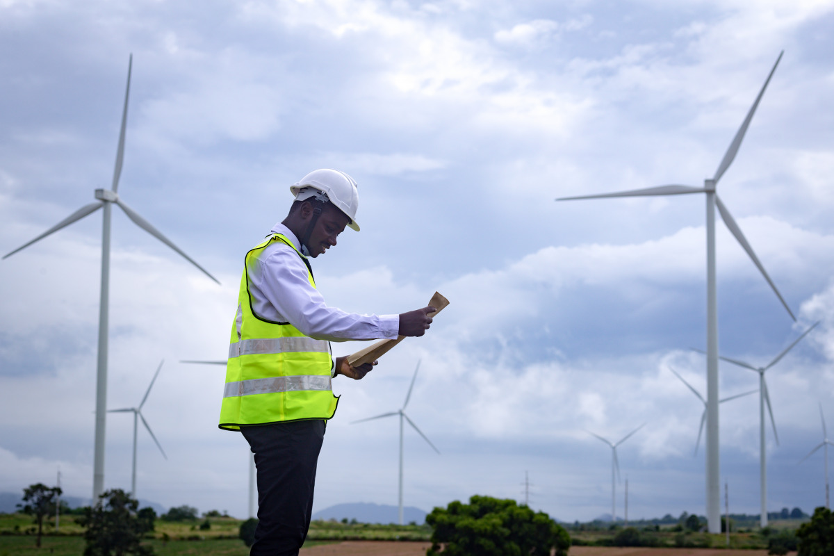 An African engineer stands in front of wind turbines.