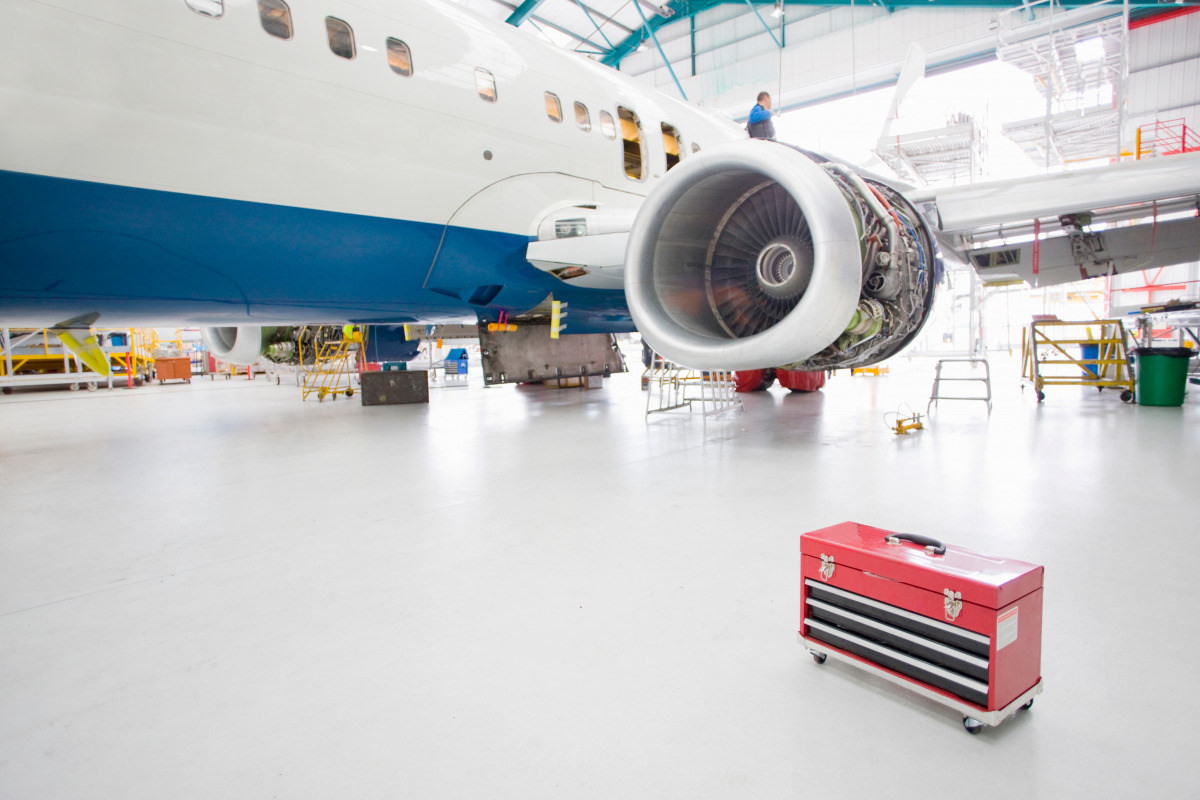 A passenger jet in a hangar with a toolbox in the foreground.