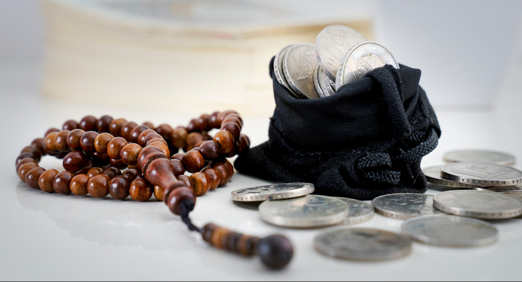 Islamic prayer beads next to a purse full of coins
