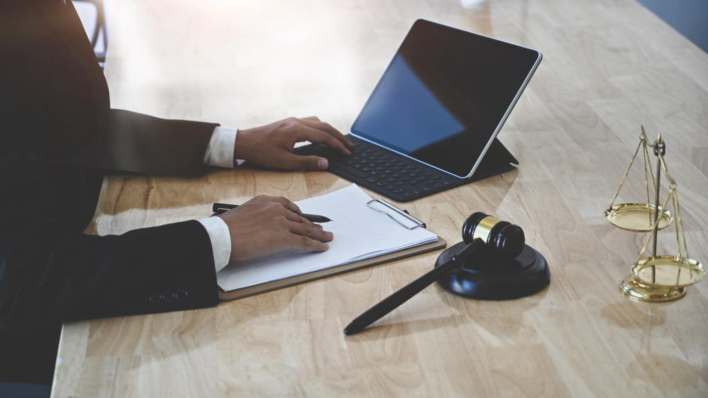 A lawyer takes notes from a tablet sitting at a desk.