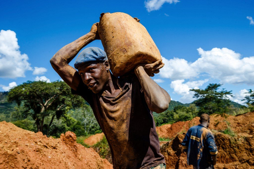 A Zimbabwean miner carries a load of ore.