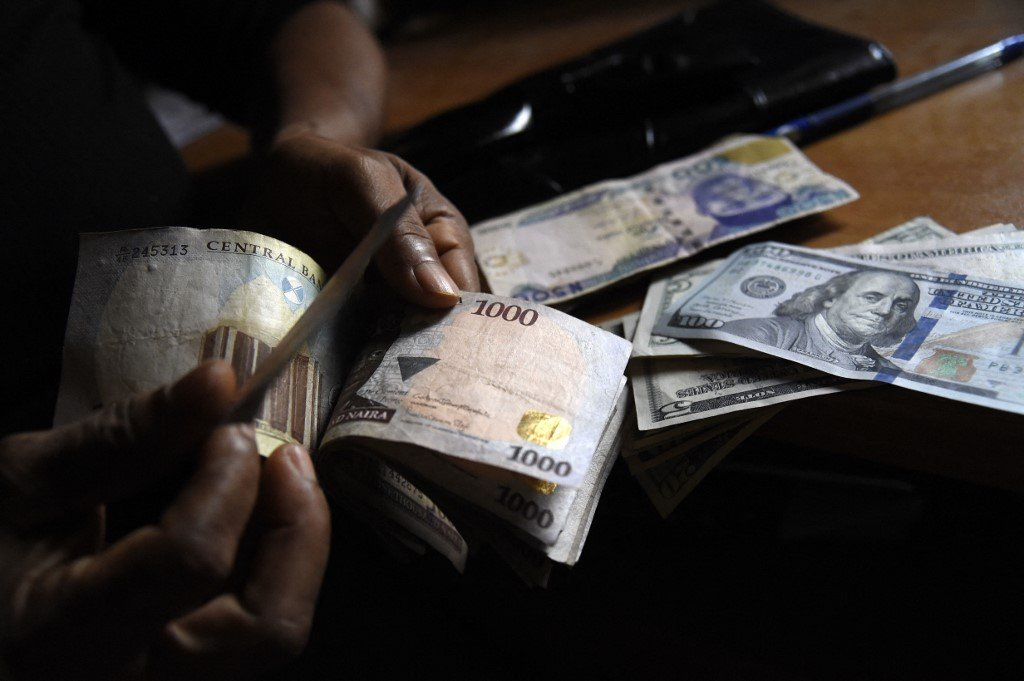 Man's hand counting naira banknotes with dollar bills on table.