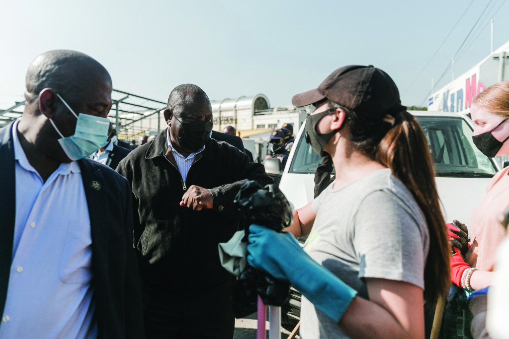 President Cyril Ramaphosa talks to volunteers in masks cleaning up riot damage.