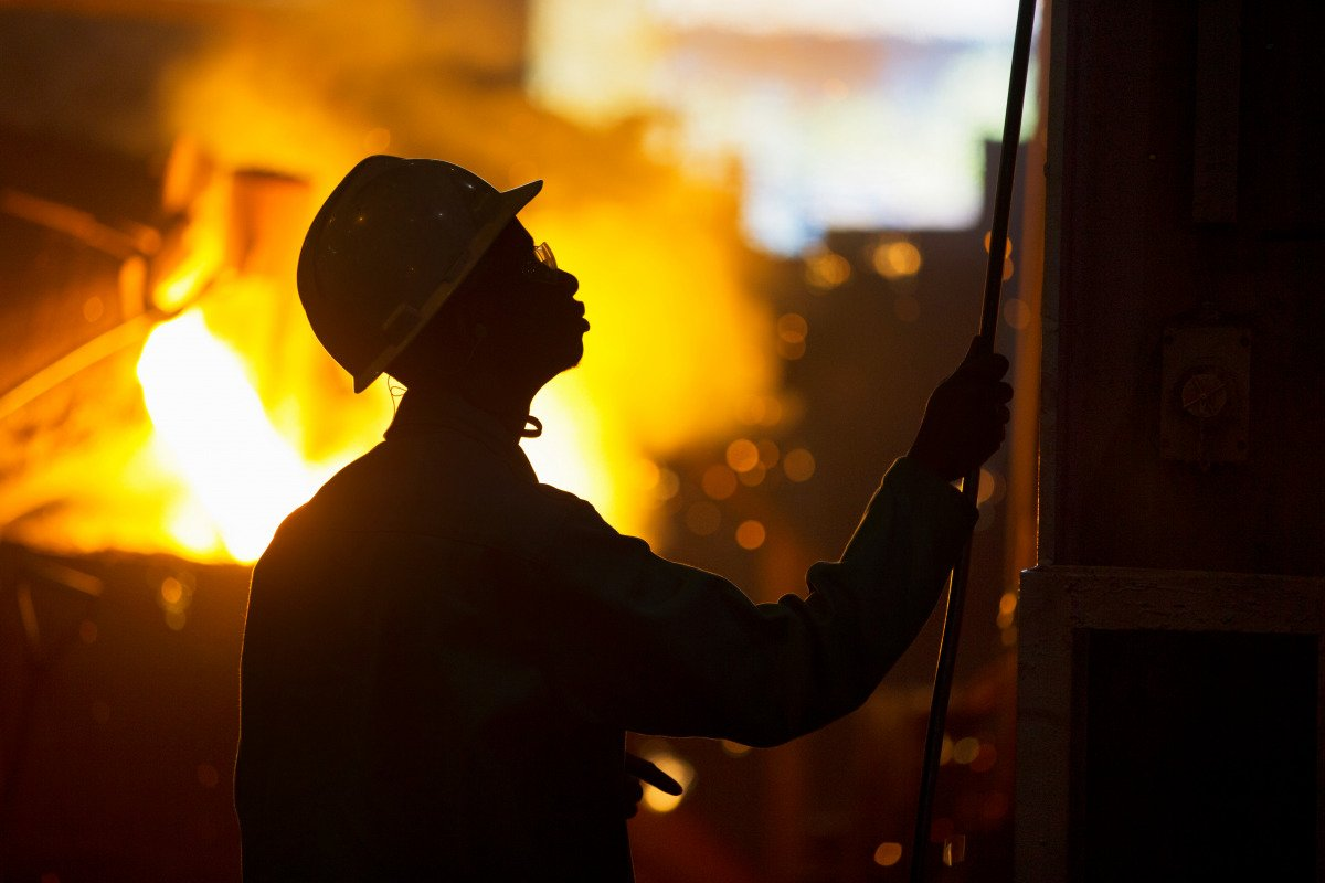 Silhouette of worker in metal foundry, with molten metal being poured in background.