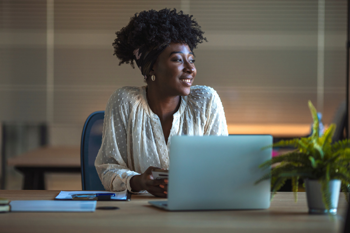 Smiling African woman looking out of the window as she works at laptop.