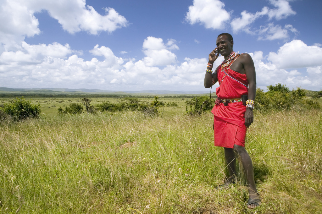 Masai man in red toga speaks on mobile phone.