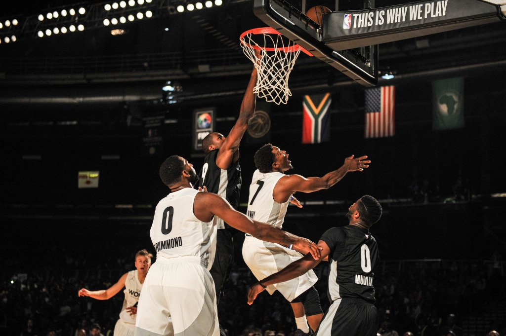 Basketball players vie for the ball.