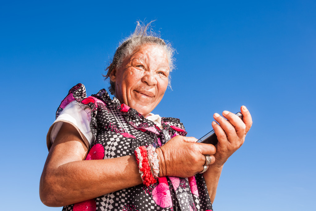 An elderly African lady holds a mobile phone.