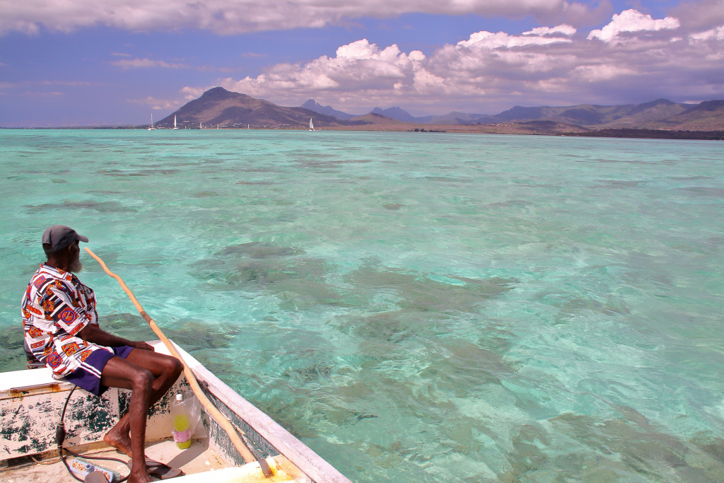 A fisherman looks across clear water to the coast of Mauritius.