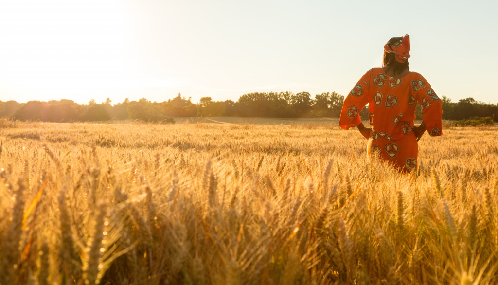 African woman in traditional clothes standing with her hands on her hips in field of wheat at sunset