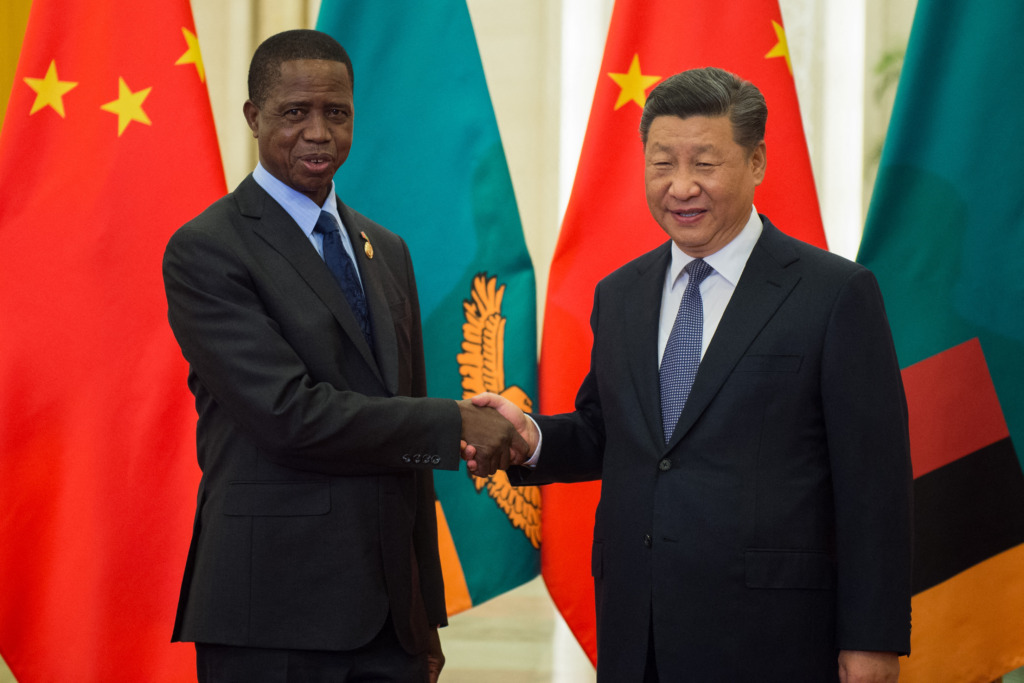 Former President Lungu of Zambia (left) shakes hands with China's Xi Jinping.