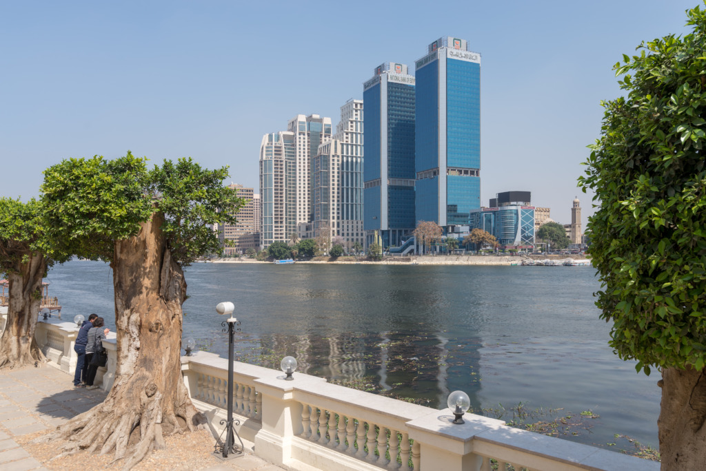 City view from River Nile overlooking Head Office of National Bank of Egypt and St. Regis hotel with two people looking at the Nile in Cairo.