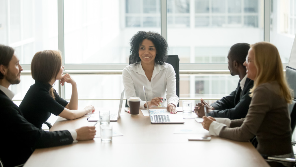 Young African woman chairs board meeting.