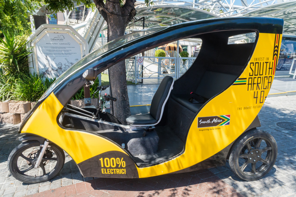 A yellow three wheeled electric vehicle in the shade of a tree at the V&A waterfront in Cape Town, South Africa.