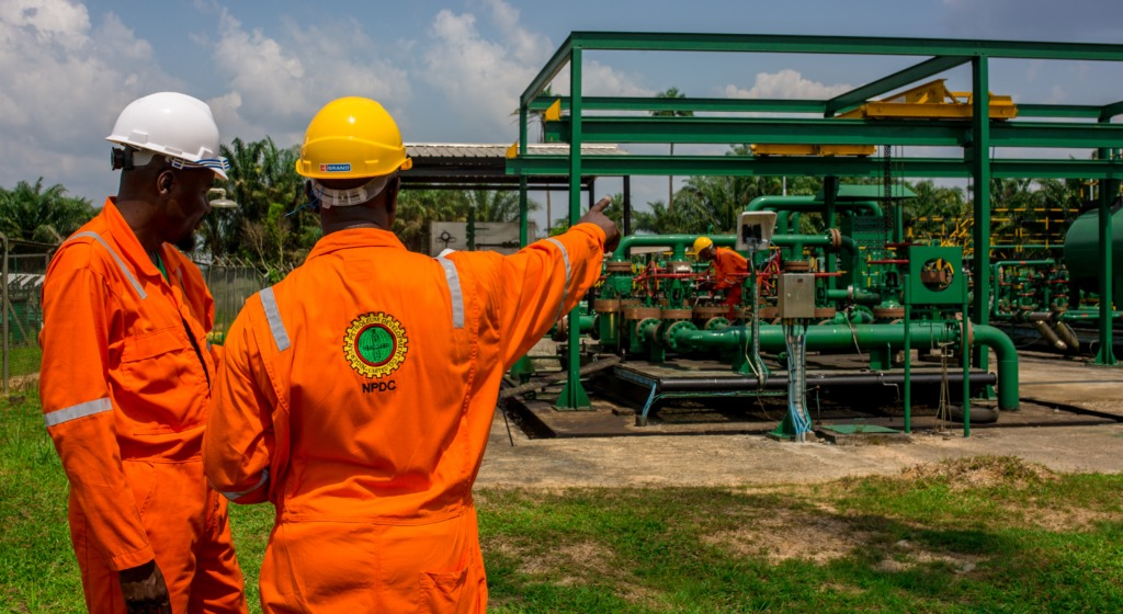 At a Nigerian oil installation, one engineer gives another instructions, indicating what needs to be done with an outstretched arm.