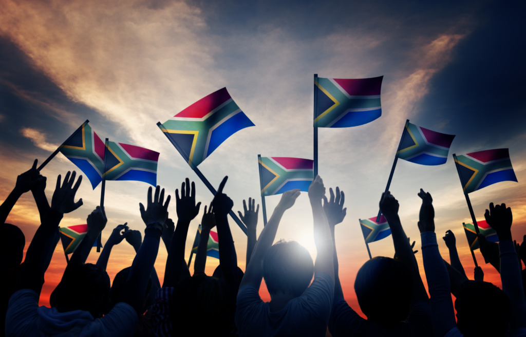Silhouettes of people waving South African flags