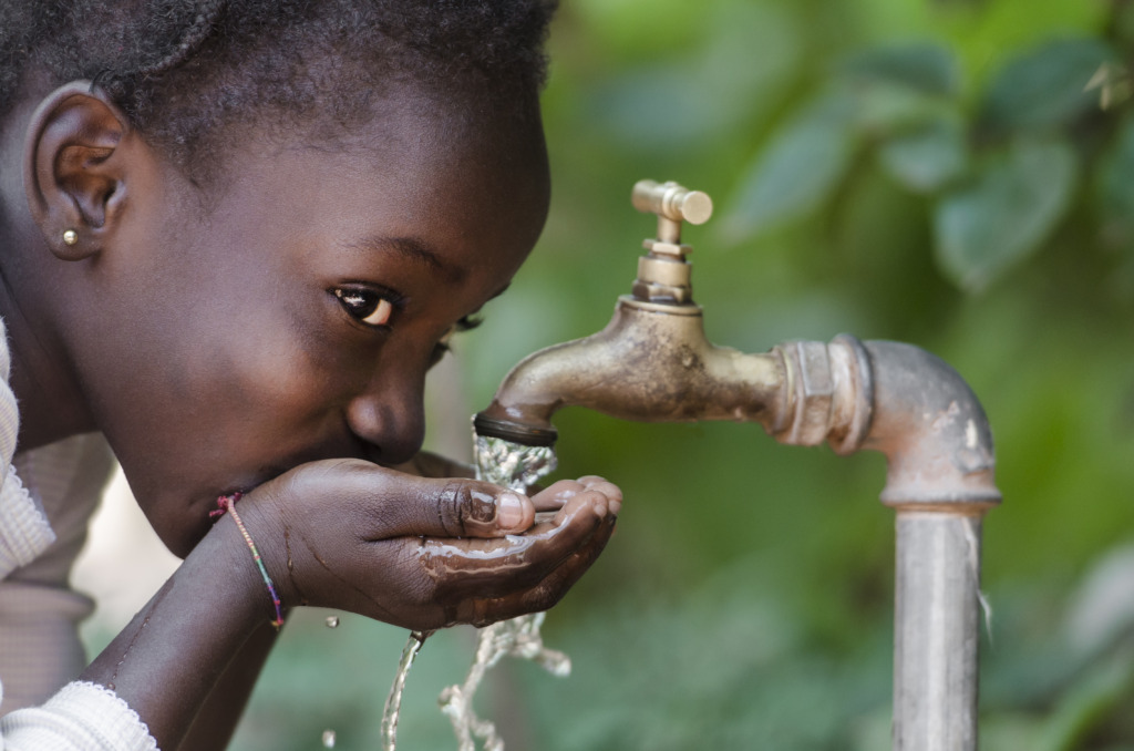 An African girl drinks water from a tap.